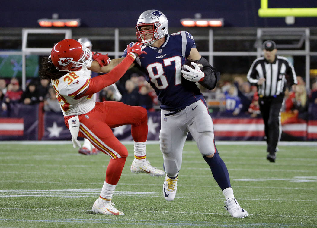 New England Patriots tight end Rob Gronkowski (87) gives a stiff arm to Kansas City Chiefs free safety Ron Parker (38) after catching a pass during the second half of an NFL football game, Sunday, ...