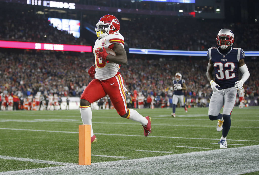Kansas City Chiefs wide receiver Tyreek Hill (10) scores a touchdown in front of New England Patriots defensive back Devin McCourty (32) after catching a pass during the second half of an NFL foot ...