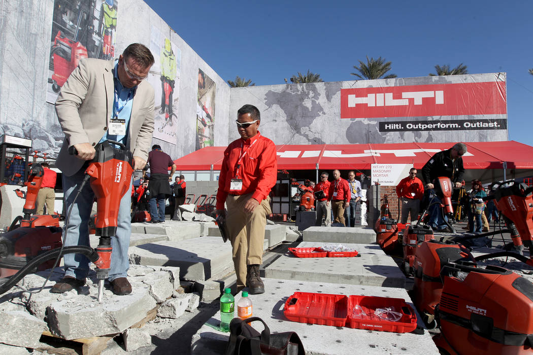 Mathew Burns of Jupiter, Fla., left, checks out a jackhammer with Hilti representative Paul Adajar during the World of Concrete show at the Las Vegas Convention Center Tuesday, Jan. 23, 2018. K.M. ...