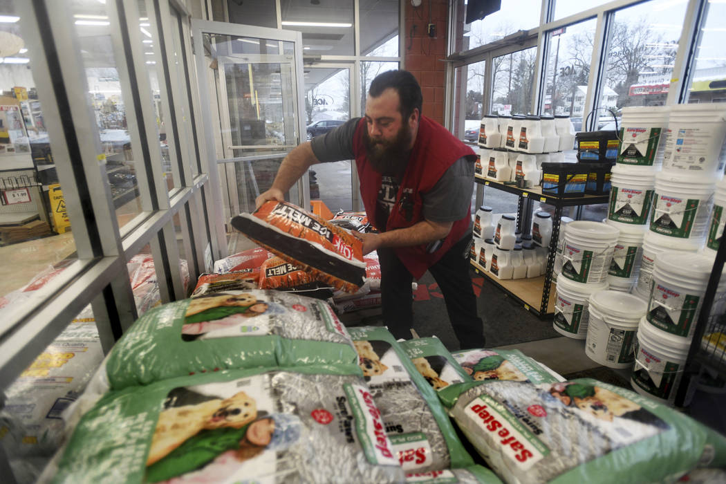 Cambria Ace Hardware sales associate Chris Thibodeau, stocks up bags of Qik Joe ice melt, Thursday, January 17, 2019, in Johnstown, Pa., in preparation for customers coming in ahead of this weeke ...