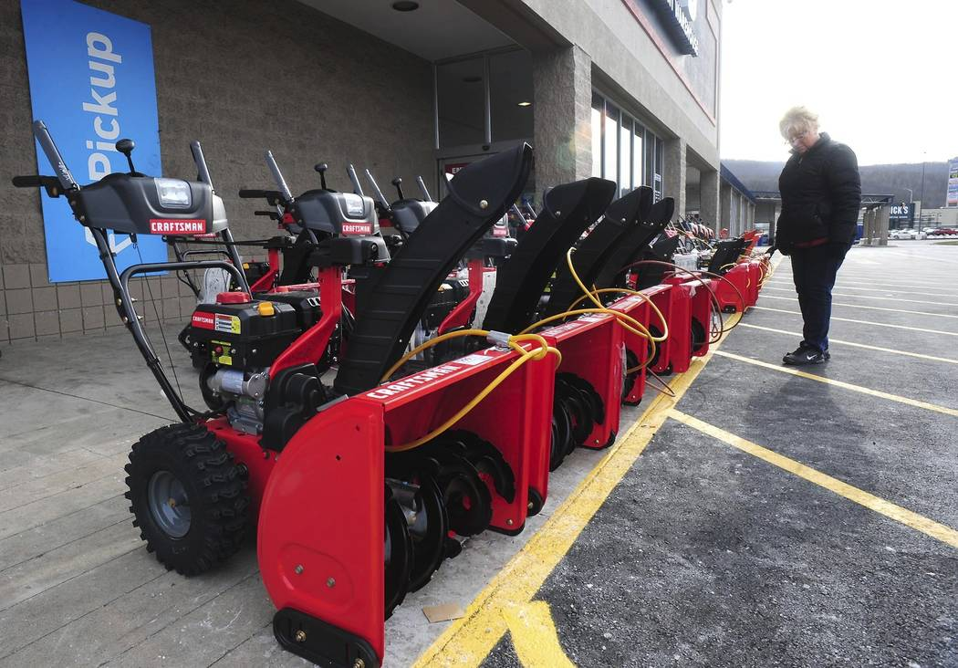Lisa Zielecki looks over snow throwers at Lowe's, Thursday, Jan. 17, 2019, in Wilkes-Barre Township, Pa. Customers were also out purchasing rock salt and ice melt Thu, in preparation for a forecas ...
