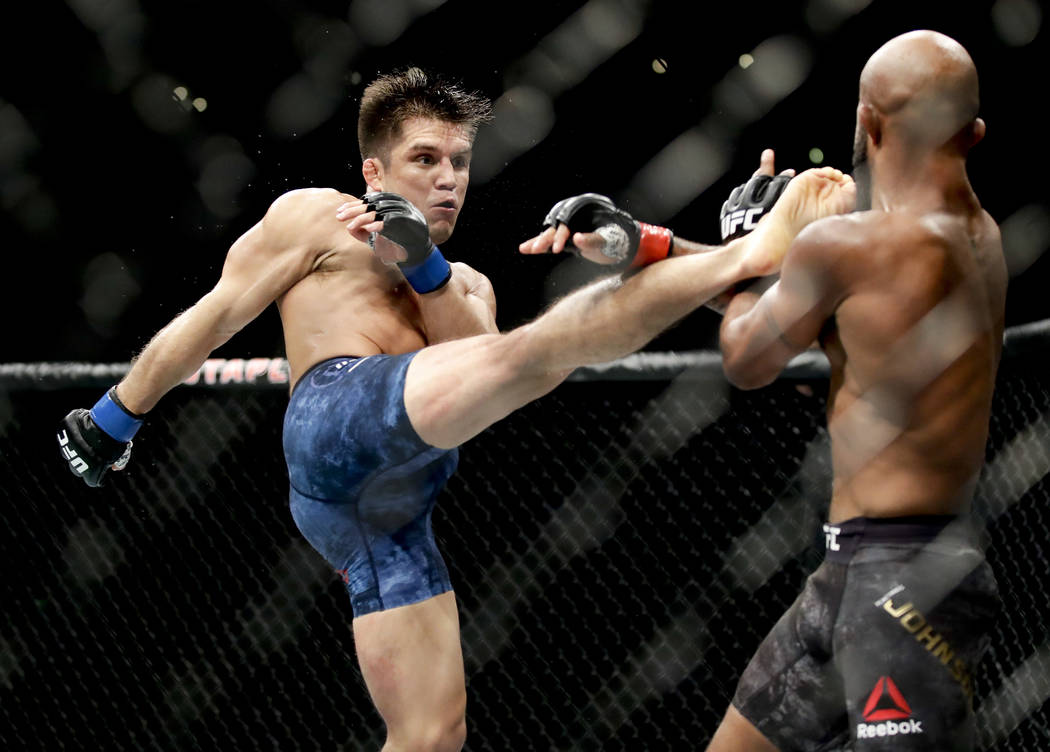 In this Aug. 4, 2018, file photo, Henry Cejudo, left, kicks Demetrious Johnson during their UFC flyweight title mixed martial arts bout at UFC 227 in Los Angeles. ESPN will raise the curtain on th ...