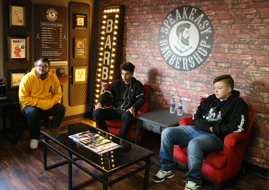 Kyle Lamb, left, waits to get a hair cut with his friend Cobe Chamorro, center, and his brother Jonathan at Speakeasy Barbershop LV at El Cortez hotel-casino on Saturday, Jan. 19, 2019, in Las Veg ...