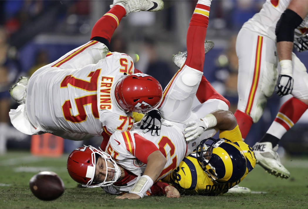 Kansas City Chiefs quarterback Patrick Mahomes, center, fumbles the ball as he is sacked by Los Angeles Rams defensive end Aaron Donald, lower right, next to Chiefs offensive guard Cameron Erving ...