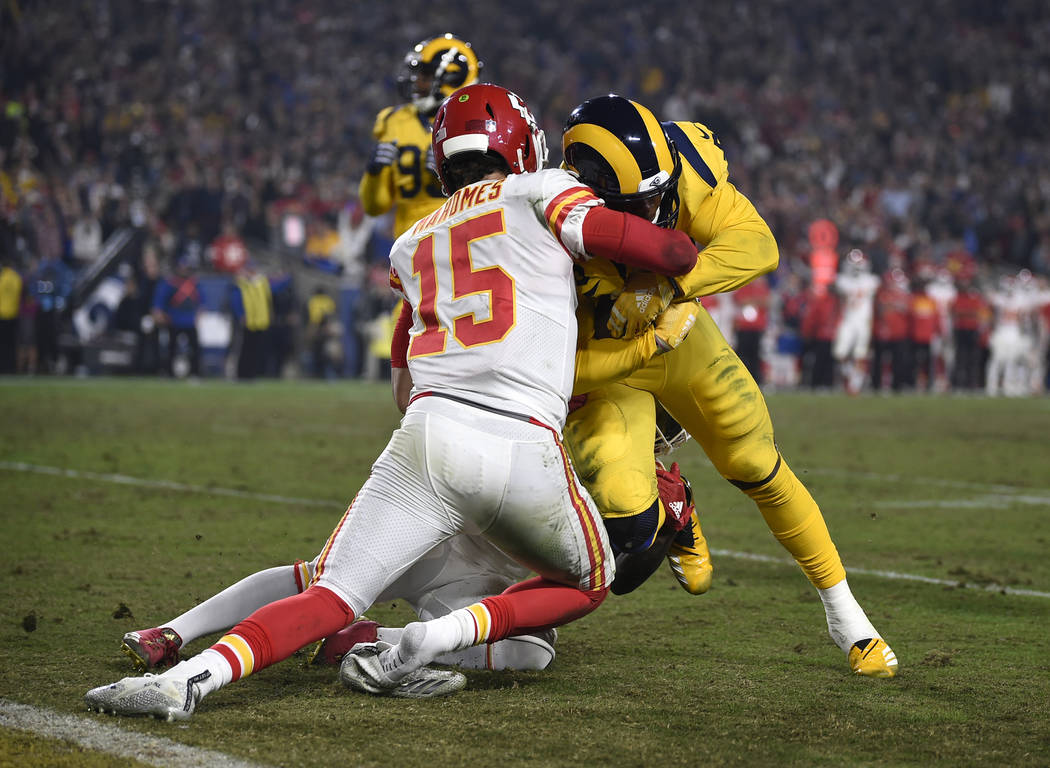 Kansas City Chiefs quarterback Patrick Mahomes (15) tries to tackle Rams outside linebacker Samson Ebukam, right, after Ebukam intercepted a pass from Mahomes during the second half of an NFL foot ...