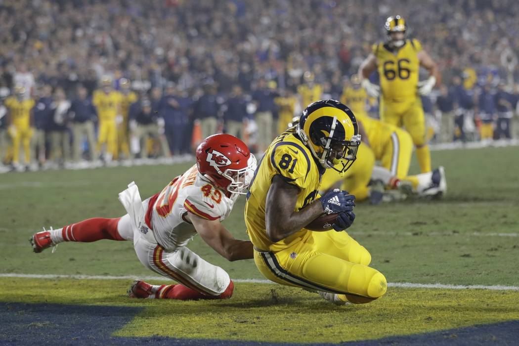Los Angeles Rams tight end Gerald Everett (81) scores a touchdown after catching a pass ahead of Kansas City Chiefs defensive back Daniel Sorensen, left, during the second half of an NFL football ...