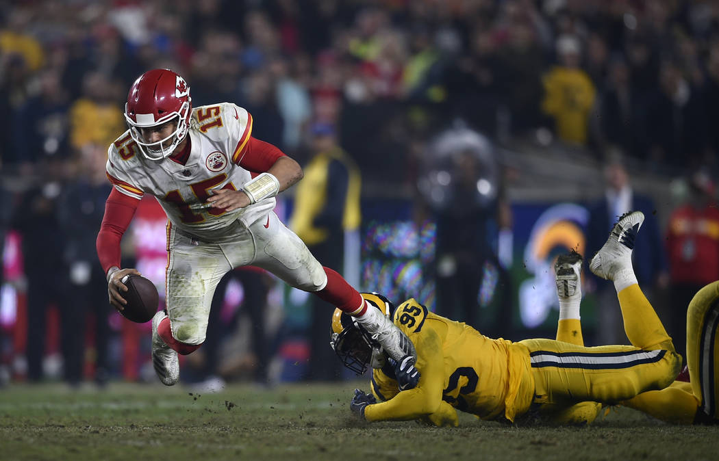 Kansas City Chiefs quarterback Patrick Mahomes (15) tries for extra yardage as he is tripped up by Los Angeles Rams defensive tackle Ethan Westbrooks, right, during the second half of an NFL footb ...