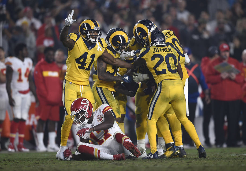 Los Angeles Rams players celebrate after cornerback Marcus Peters (obscured) intercepted a pass intended for Kansas City Chiefs wide receiver Chris Conley, lower left, during the second half of an ...