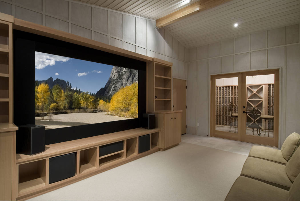 A wine-tasting room is adjacent to this home theater room that features a big screen and built-in shelves. (Getty Images)
