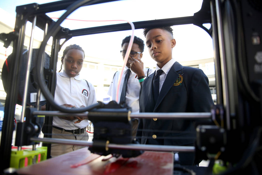 Rainbow Dreams Academy sixth-graders, from left, Marcel Elzy, 11, Wayne Harper, 12, and Nehemiah Mayfield, 11, check out a 3D printer during the the first Dr. Martin Luther King Jr. Technology Sum ...