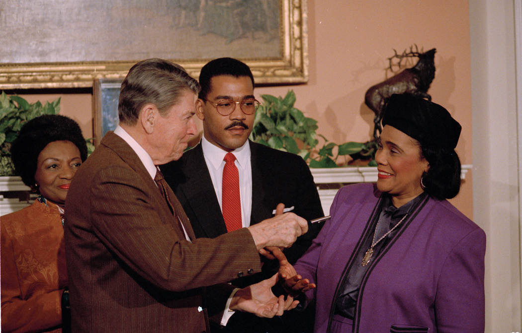 President Reagan hands Coretta Scott King the pen he used to sign the Martin Luther King, Jr. Day proclamation at the White House, Jan. 12, 1988. Witnessing the gesture is King's son, Dexter King ...