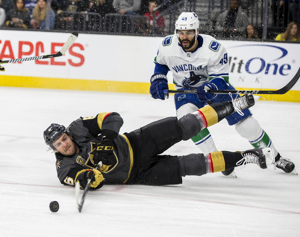 Golden Knights defenseman Colin Miller (6) deflects the puck away as he slides on the ground with Vancouver Canucks right wing Darren Archibald (49) close behind during the second period of an NHL ...