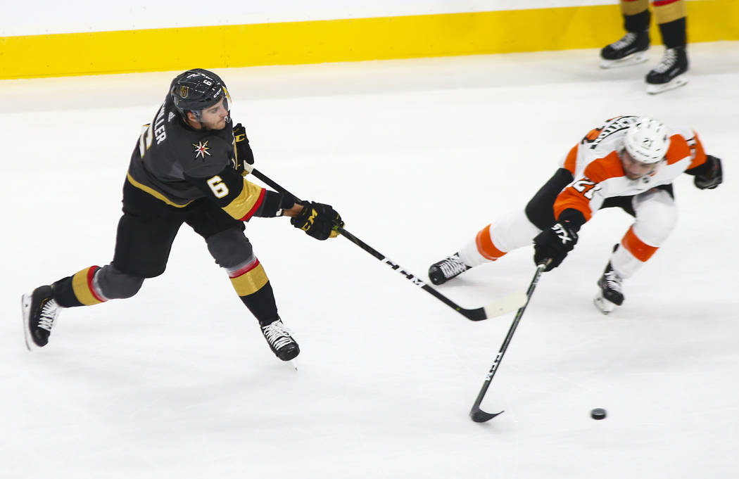 Golden Knights defenseman Colin Miller (6) sends the puck past Philadelphia Flyers center Scott Laughton (21) during the first period of a season-opening game at T-Mobile Arena in Las Vegas on Thu ...