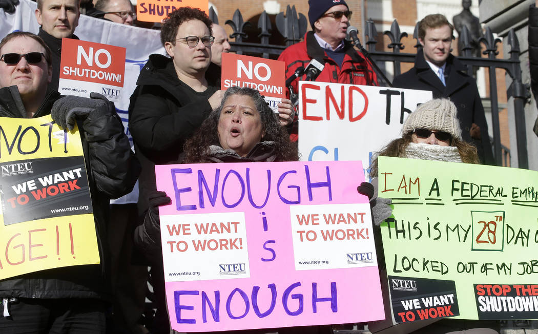 Internal Revenue Service employees, front row from the left, Brian Lanouette, of Merrimack, N.H., Mary Maldonado, of Dracut, Mass., and Maria Zangari, of Haverhill, Mass., display placards during ...