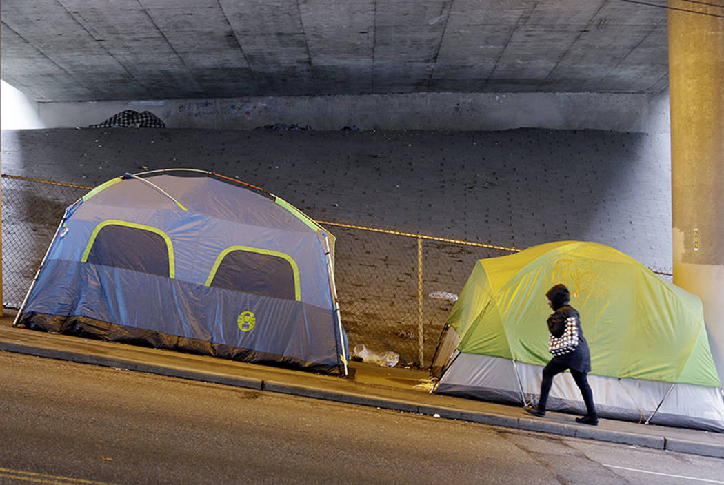 A person walks up a hill next to tents lined up beneath a highway and adjacent to downtown Seattle in March 2017. (AP Photo/Elaine Thompson, File)