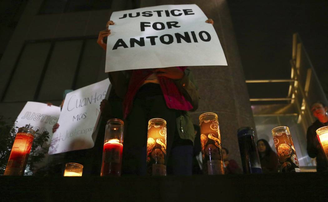 Family members and others stand in front of the Tempe Police headquarters to hold a protest and vigil for a 14-year-old boy who was shot to death by Tempe Police on Tuesday, as police say they wer ...