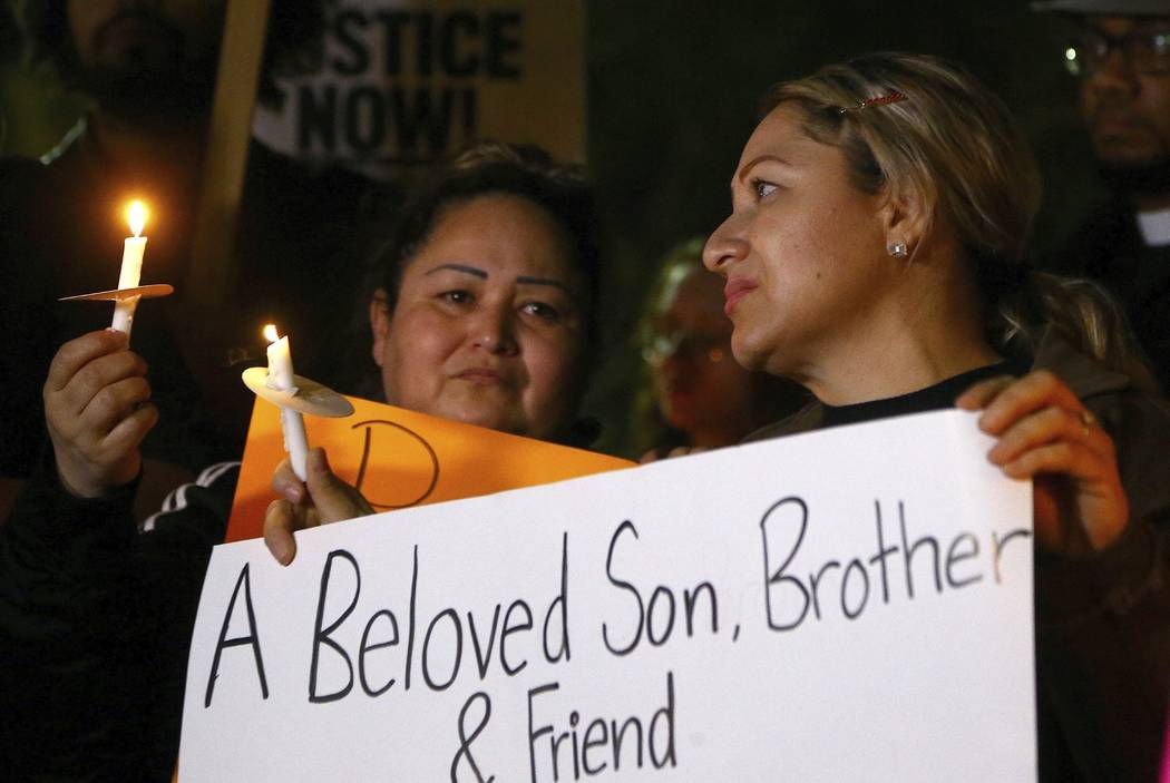 Sandra Gonzalez, left, mother of slain 14-year-old boy shot by Tempe Police, joins another family member, right, and others in front of the Tempe Police headquarters to hold a protest and vigil fo ...