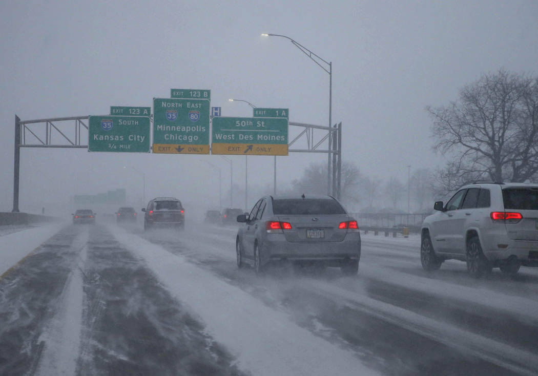 Vehicles travel along Interstate 80 as heavy snow falls, Friday, Jan. 18, 2019, in in West Des Moines, Iowa. (Bryon Houlgrave/The Des Moines Register via AP)