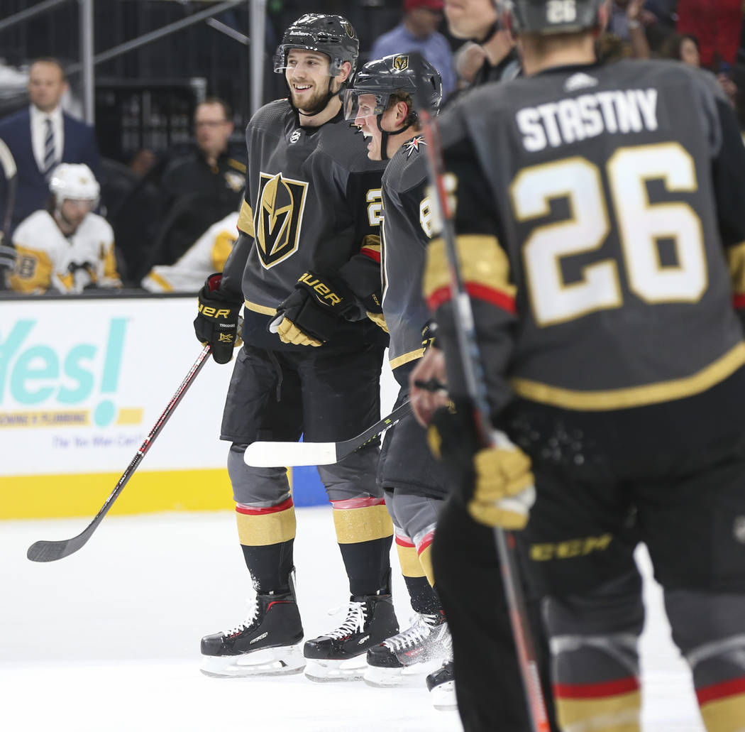 Golden Knights defenseman Shea Theodore, left, celebrates his goal with Golden Knights defenseman Nate Schmidt during the first period of an NHL hockey game against the Pittsburgh Penguins at T-Mo ...
