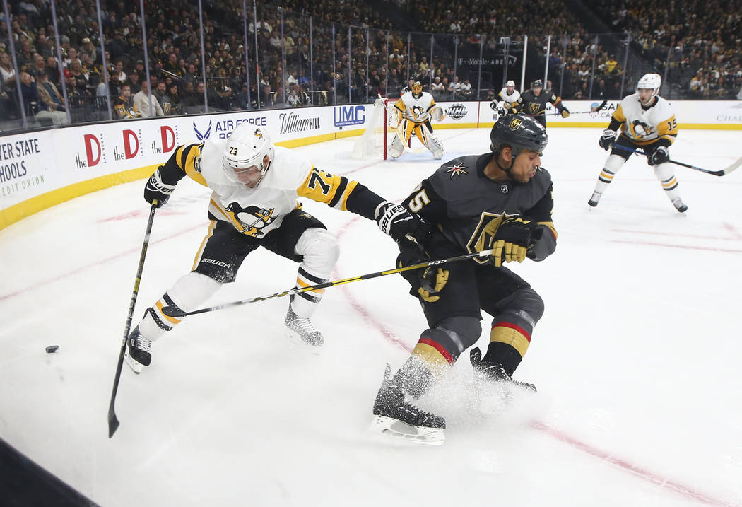 Golden Knights right wing Ryan Reaves (75) battles for the puck against Pittsburgh Penguins defenseman Jack Johnson (73) during the first period of an NHL hockey game at T-Mobile Arena in Las Vega ...