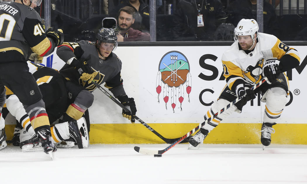 Pittsburgh Penguins right wing Phil Kessel (81) moves the puck past Golden Knights center Cody Eakin (21) during the first period of an NHL hockey game at T-Mobile Arena in Las Vegas on Saturday, ...