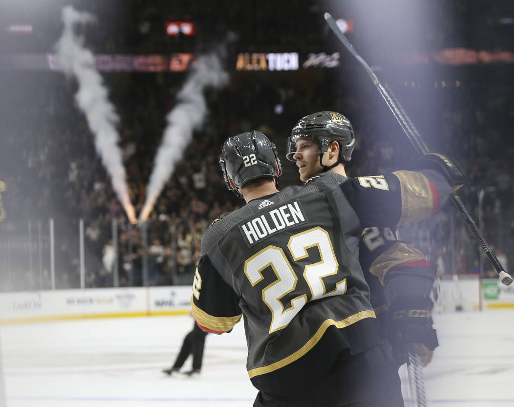 Golden Knights defenseman Nick Holden (22) celebrates a goal by center Oscar Lindberg during the first period of an NHL hockey game against the Pittsburgh Penguins at T-Mobile Arena in Las Vegas ...