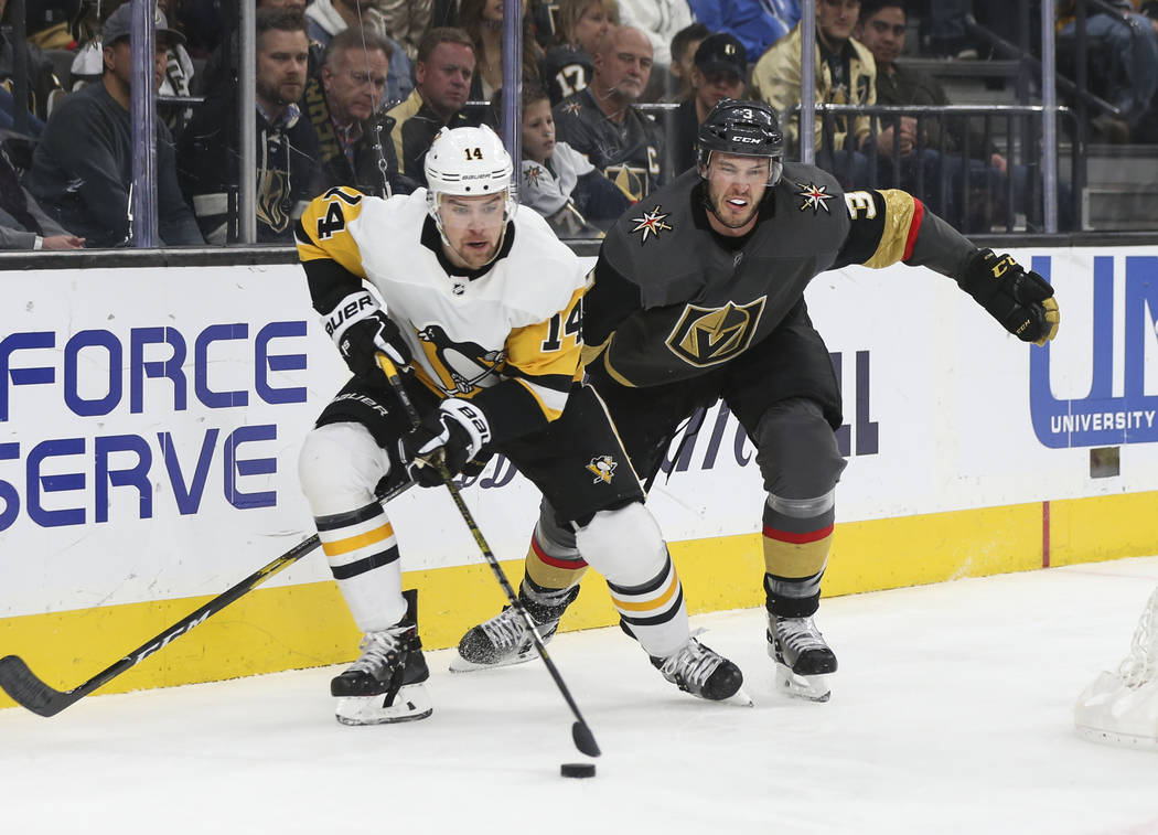 Pittsburgh Penguins left wing Tanner Pearson (14) moves the puck in front of Golden Knights defenseman Brayden McNabb (3) during the second period of an NHL hockey game at T-Mobile Arena in Las Ve ...