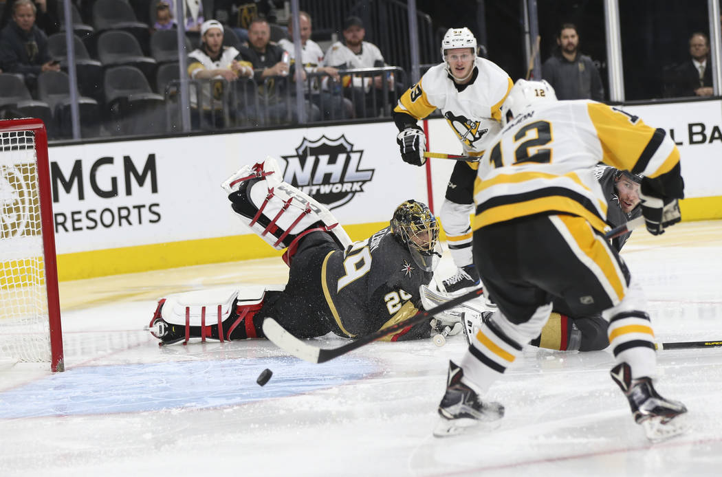 Pittsburgh Penguins center Dominik Simon (12) sends the puck into the net past Golden Knights goaltender Marc-Andre Fleury (29) during the second period of an NHL hockey game at T-Mobile Arena in ...