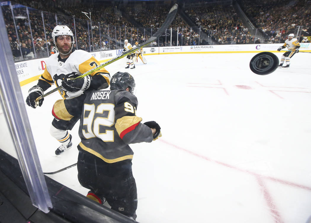 Pittsburgh Penguins center Matt Cullen (7) sends the puck past Golden Knights left wing Tomas Nosek (92) during the third period of an NHL hockey game at T-Mobile Arena in Las Vegas on Saturday, J ...