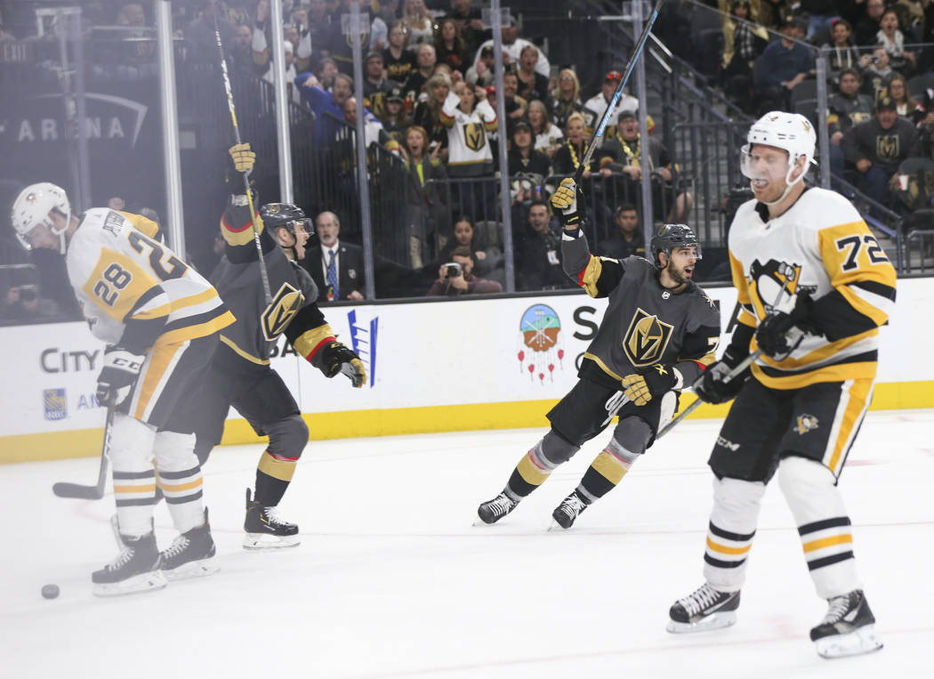 Golden Knights players Jonathan Marchessault, left, and Brandon Pirri celebrate a goal by William Karlsson, not pictured, during the third period of an NHL hockey game against the Pittsburgh Pengu ...