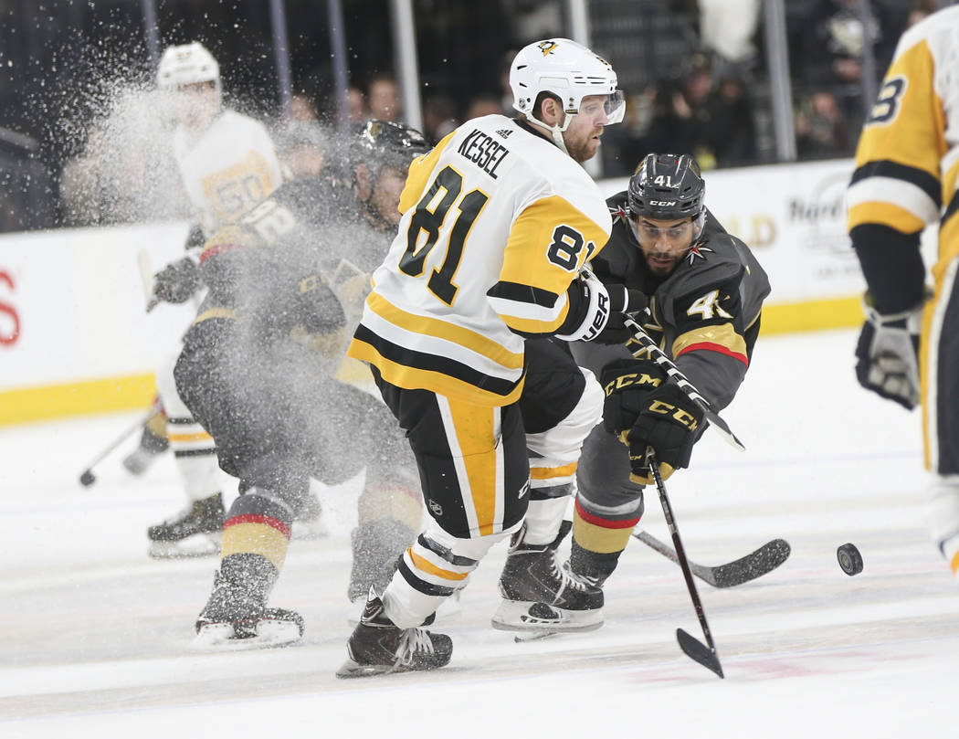 Golden Knights center Pierre-Edouard Bellemare (41) sends the puck past Pittsburgh Penguins right wing Phil Kessel (81) during the third period of an NHL hockey game at T-Mobile Arena in Las Vegas ...