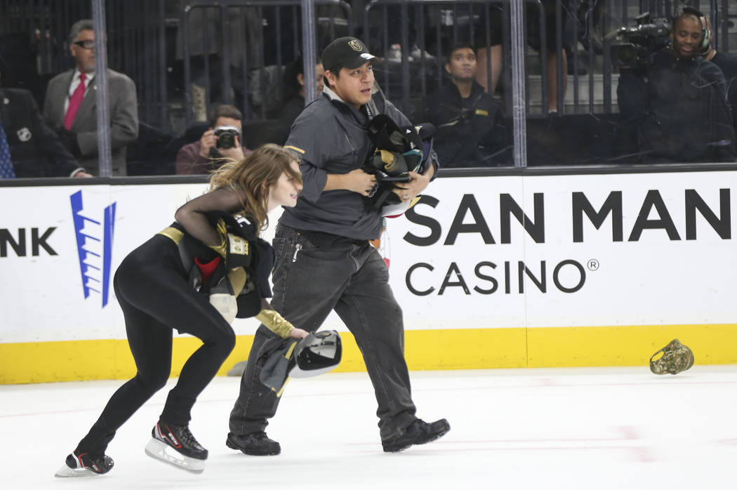Members of the Golden Knights ice crew pick up hats on the ice that were thrown in celebration of a hat trick by Jonathan Marchessault, not pictured, during the third period of an NHL hockey game ...