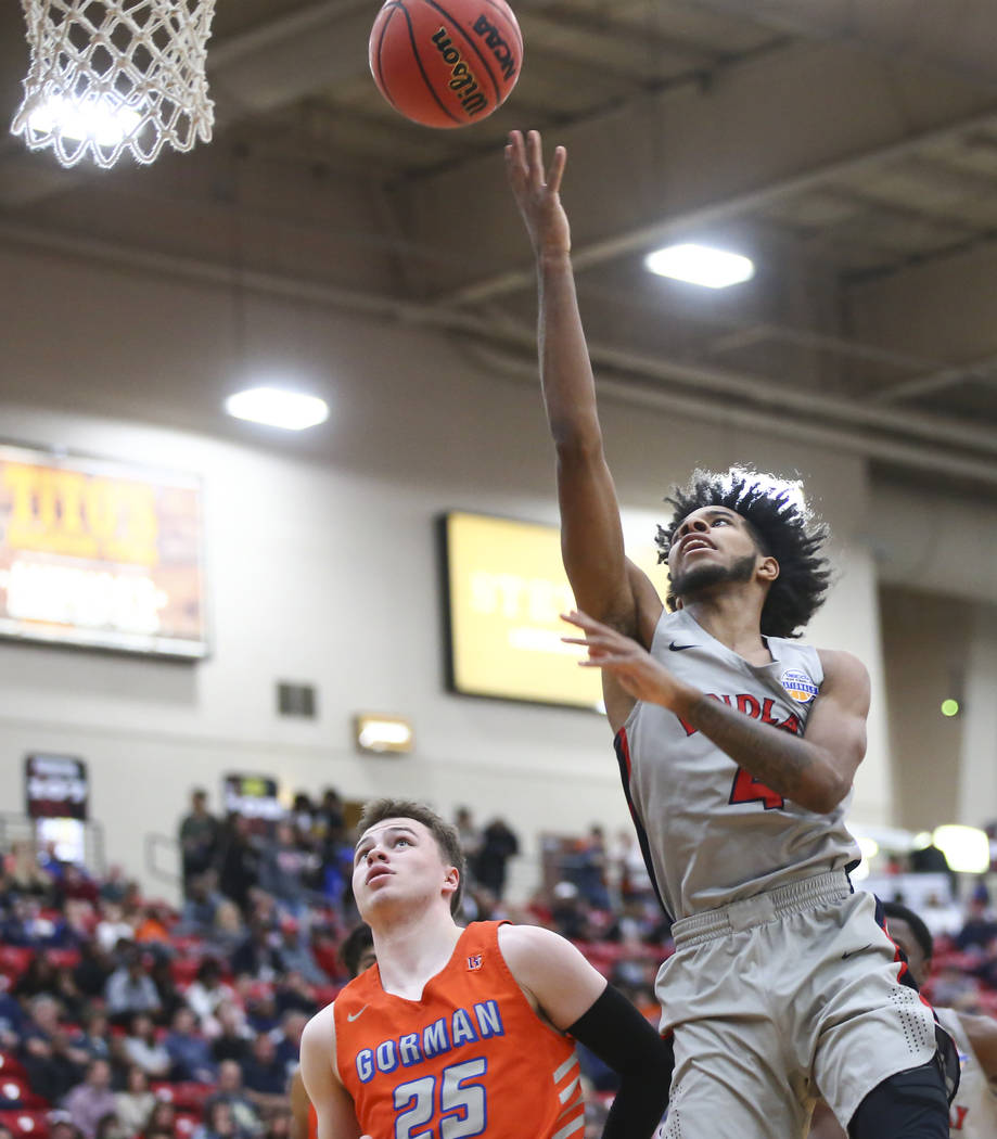 Findlay Prep's P.J. Fuller goes to the basket against Bishop Gorman's Chance Michels (25) during the second half of the annual Big City Showdown basketball game at the South Point in Las Vegas on ...