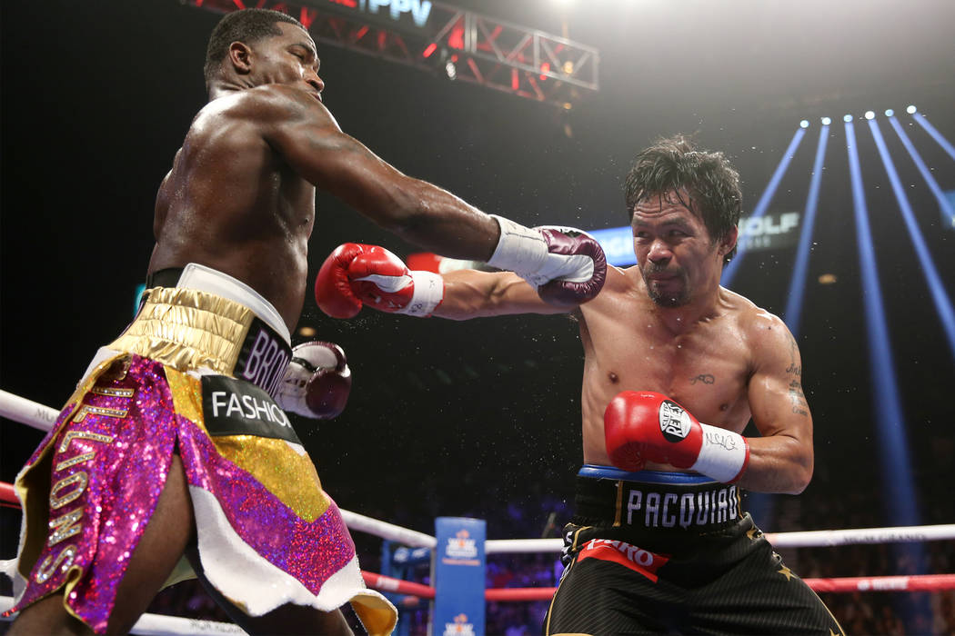 Adrien Broner, left, battles Manny Pacquiao in the WBA Welterweight title bout at the MGM Grand Garden Arena in Las Vegas, Saturday, Jan. 19, 2019. Pacquiao won by unanimous decision. (Erik Verduz ...