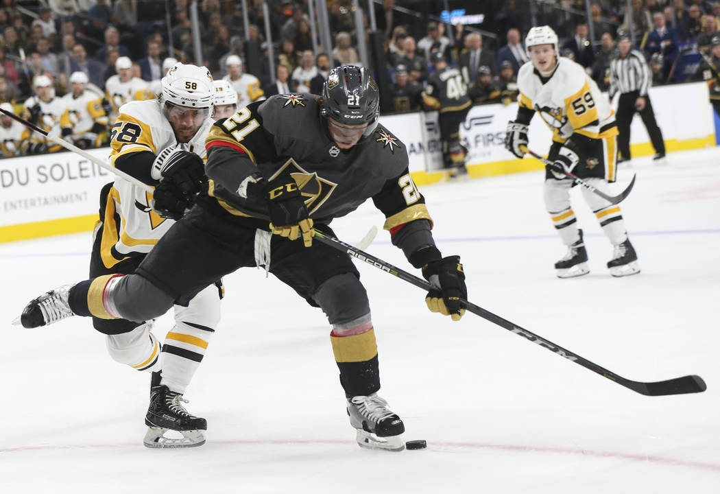 Golden Knights center Cody Eakin (21) battles for the puck against Pittsburgh Penguins defenseman Kris Letang (58) during the first period of an NHL hockey game at T-Mobile Arena in Las Vegas on S ...