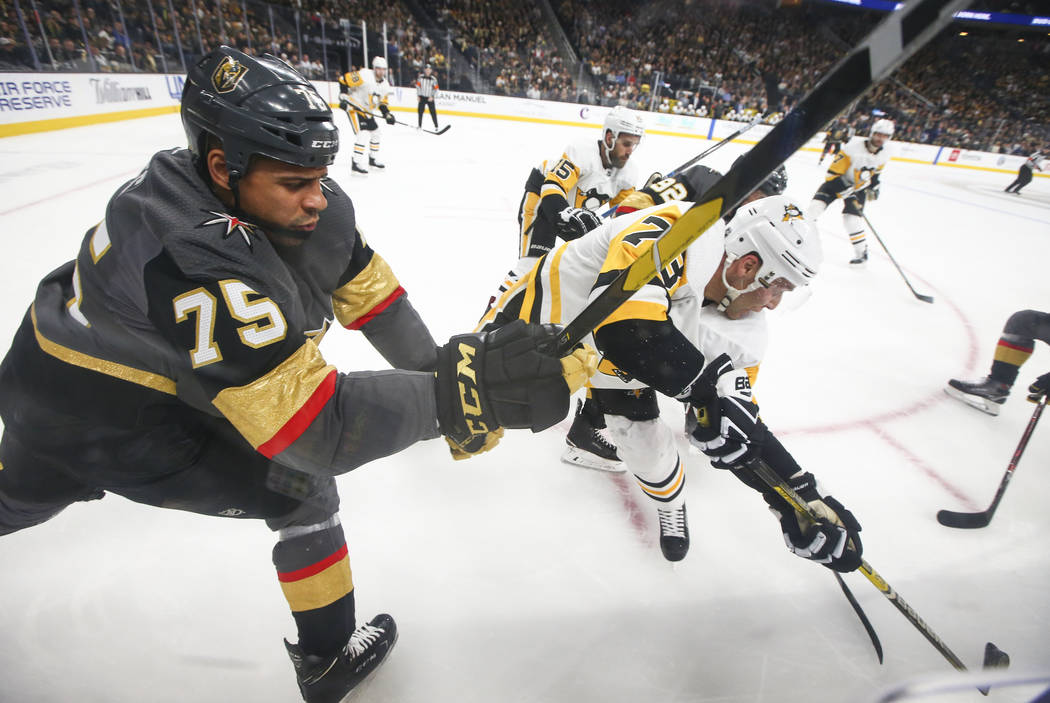Golden Knights right wing Ryan Reaves (75) and Pittsburgh Penguins defenseman Jack Johnson (73) battle for the puck during the first period of an NHL hockey game at T-Mobile Arena in Las Vegas on ...