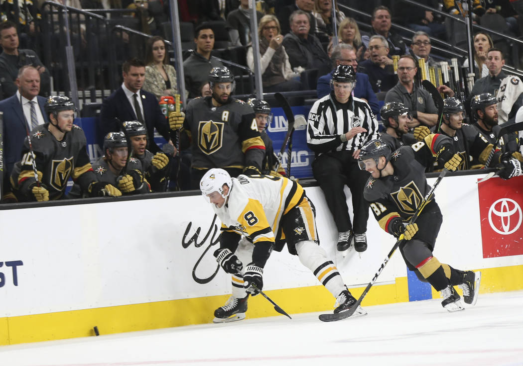 Golden Knights center Jonathan Marchessault (81) chases after the puck next to Pittsburgh Penguins defenseman Brian Dumoulin (8) during the third period of an NHL hockey game at T-Mobile Arena in ...