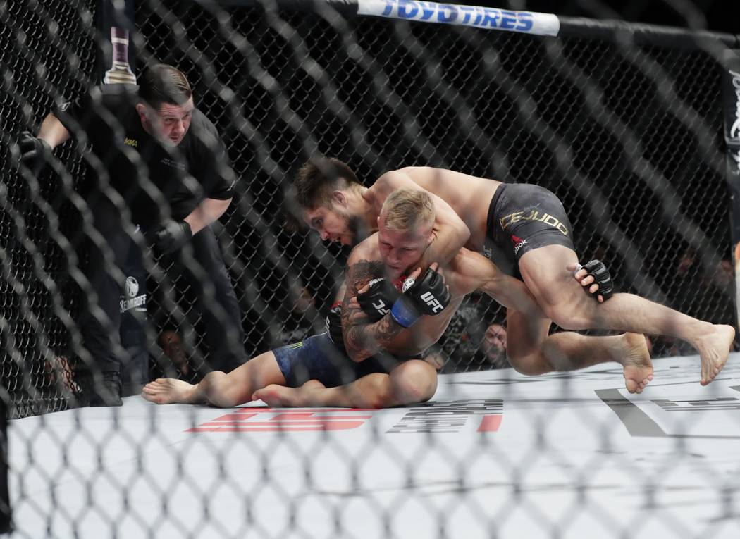 Henry Cejudo, right, wrestles with TJ Dillashaw during the first round of a flyweight mixed martial arts championship bout at UFC Fight Night early Sunday, Jan. 20, 2019, in New York. Cejudo stopp ...