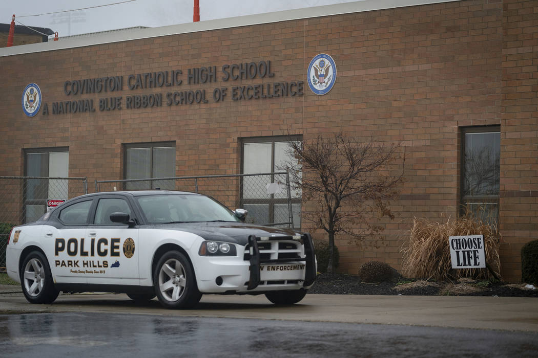 A police car sits in front of Covington Catholic High School in Park Hills, Ky., Saturday, Jan 19, 2019. A diocese in Kentucky apologized Saturday after videos emerged showing students from the Ca ...