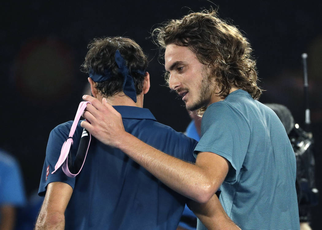 Greece's Stefanos Tsitsipas, right, is congratulated by Switzerland's Roger Federer after winning their fourth round match at the Australian Open tennis championships in Melbourne, Australia, Sund ...