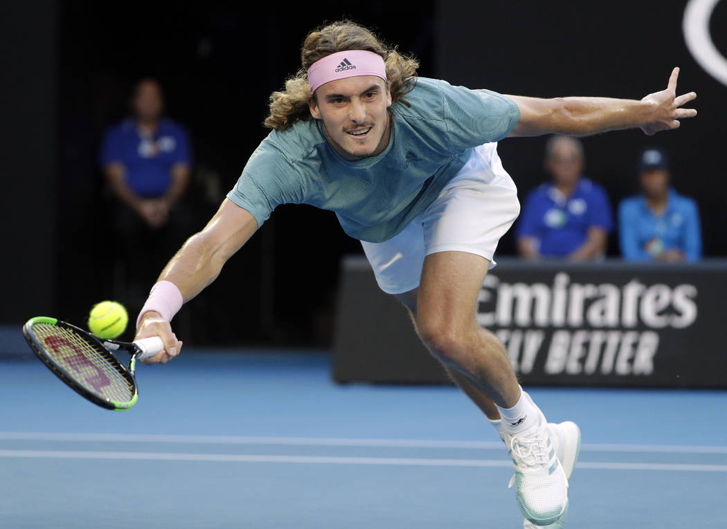 Greece's Stefanos Tsitsipas makes a forehand return to Switzerland's Roger Federer during their fourth round match at the Australian Open tennis championships in Melbourne, Australia, Sunday, Jan. ...