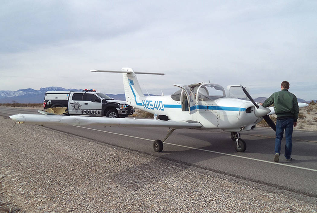 Law enforcement officers surround a plane that made an emergency landing on Kyle Canyon Road, near Las Vegas, on Sunday, Jan. 20, 2019. (Nevada Highway Patrol)