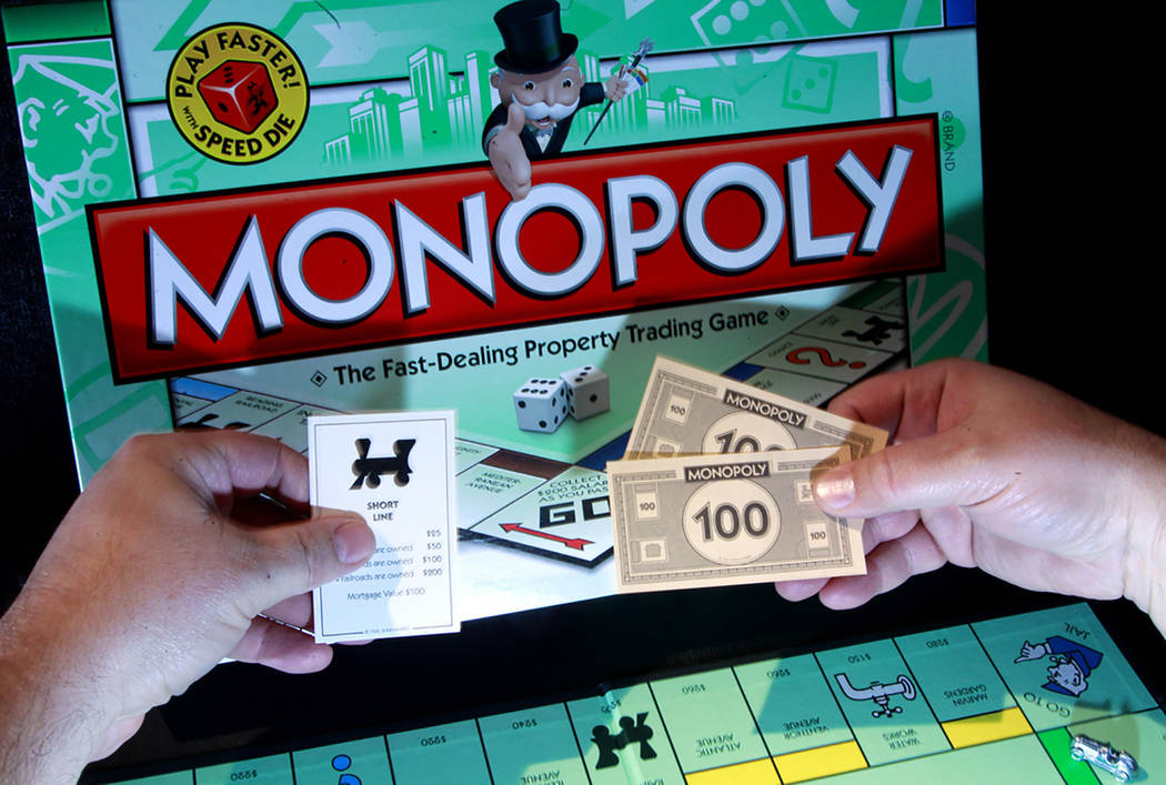 """A board, big bills and cards are among the elements of the game """"Monopoly."""" (The Associated Press file)"""