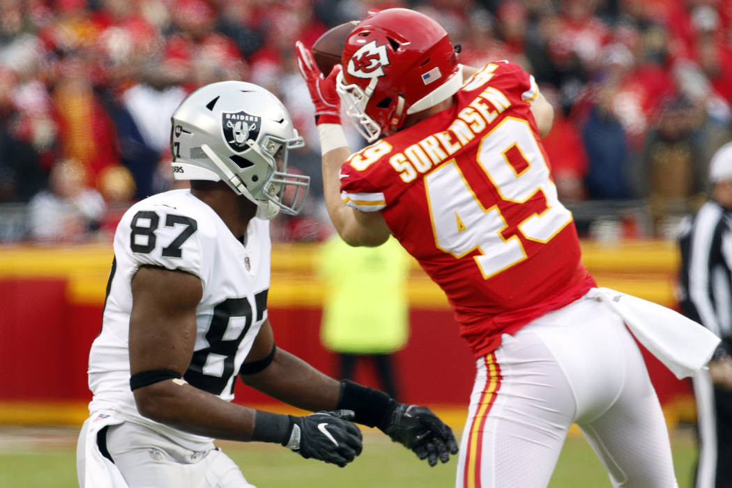 Kansas City Chiefs defensive back Daniel Sorensen (49) intercepts a pass intended for Oakland Raiders tight end Jared Cook (87) during the first half of an NFL football game in Kansas City, Mo., S ...