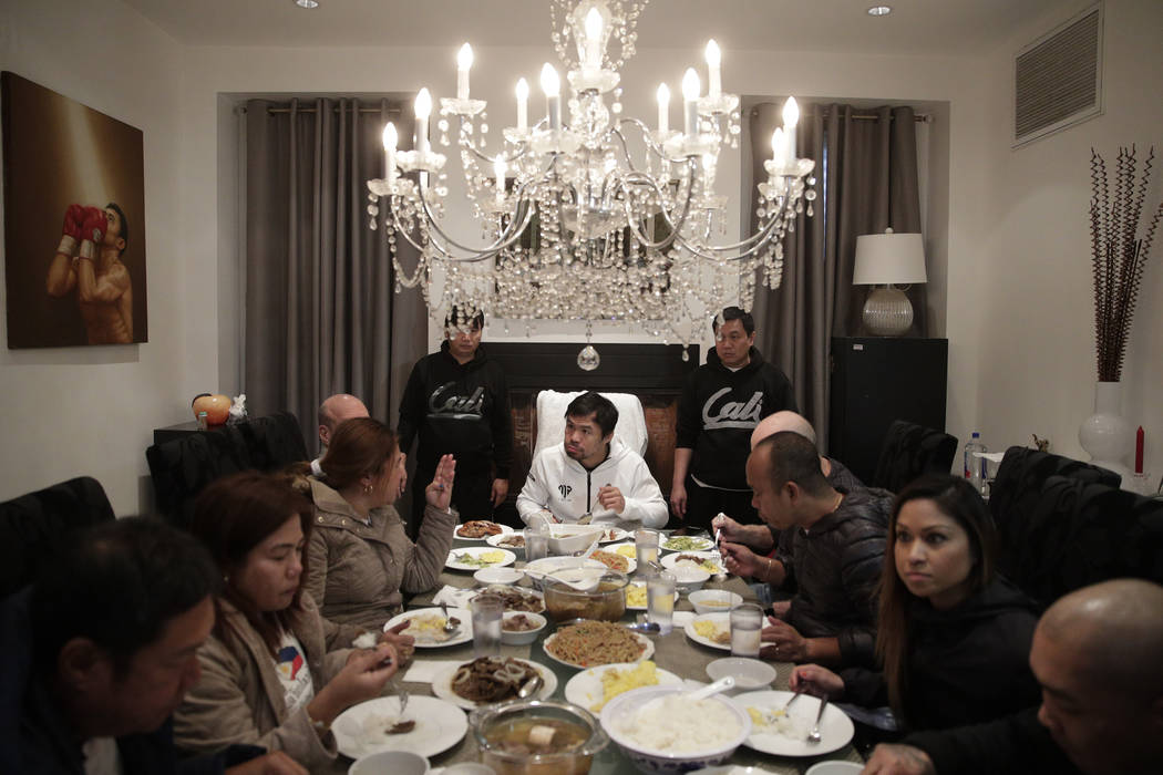 In this Jan. 14, 2019, file photo, boxer Manny Pacquiao, center, eats breakfast with friends and relatives following his morning run in Los Angeles. (AP Photo/Jae C. Hong, File)