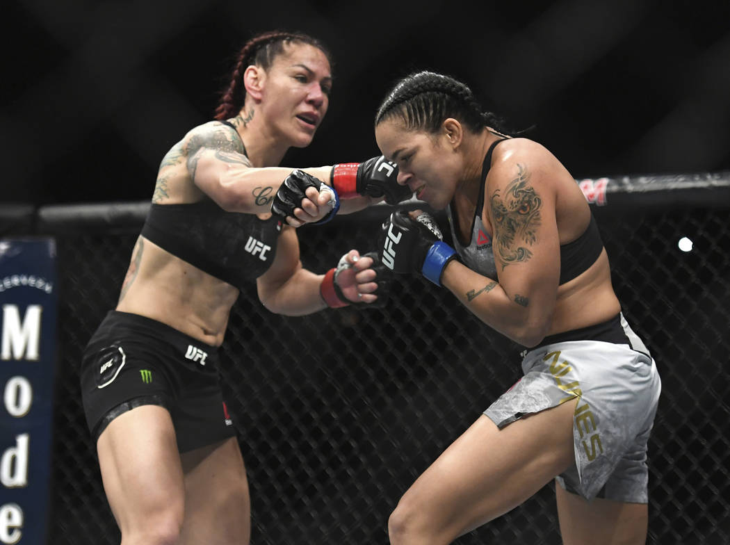 Cris Cyborg, left, and Amanda Nunes exchange punches during the first round of a featherweight mixed martial arts bout at UFC 232, Saturday, Dec. 29, 2018, in Inglewood, Calif. (AP Photo/Kyusung Gong)