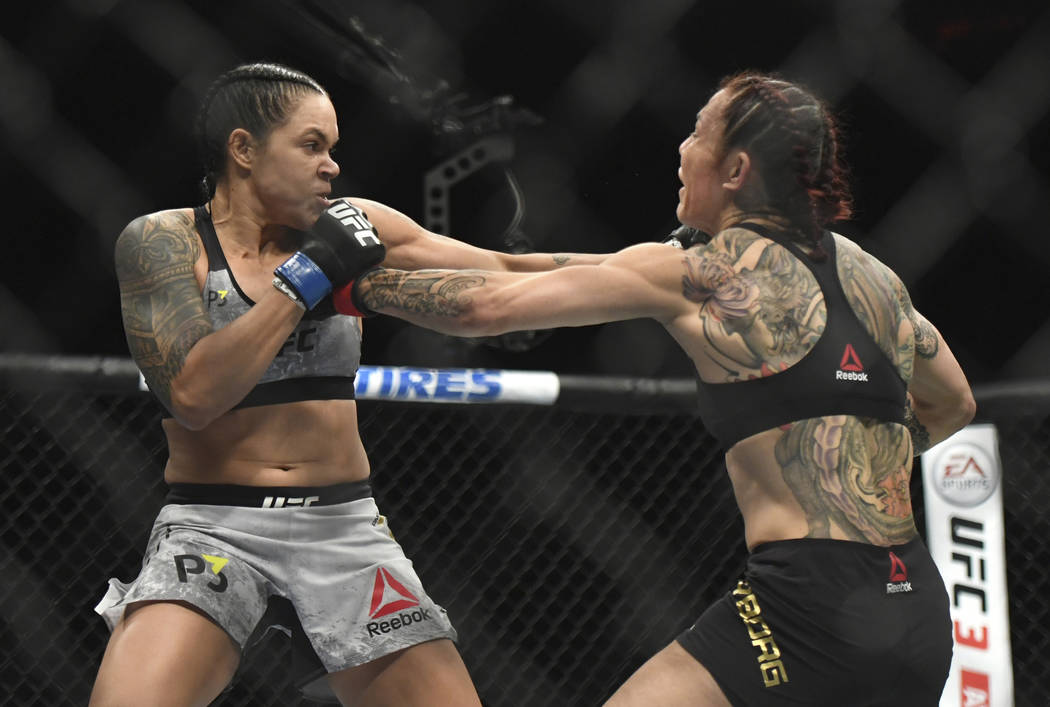 Amanda Nunues, left, lands a punch to Cris Cyborg during the first round of a featherweight title mixed martial arts bout at UFC 232, Saturday, Dec. 29, 2018, in Inglewood, Calif. (AP Photo/Kyusun ...