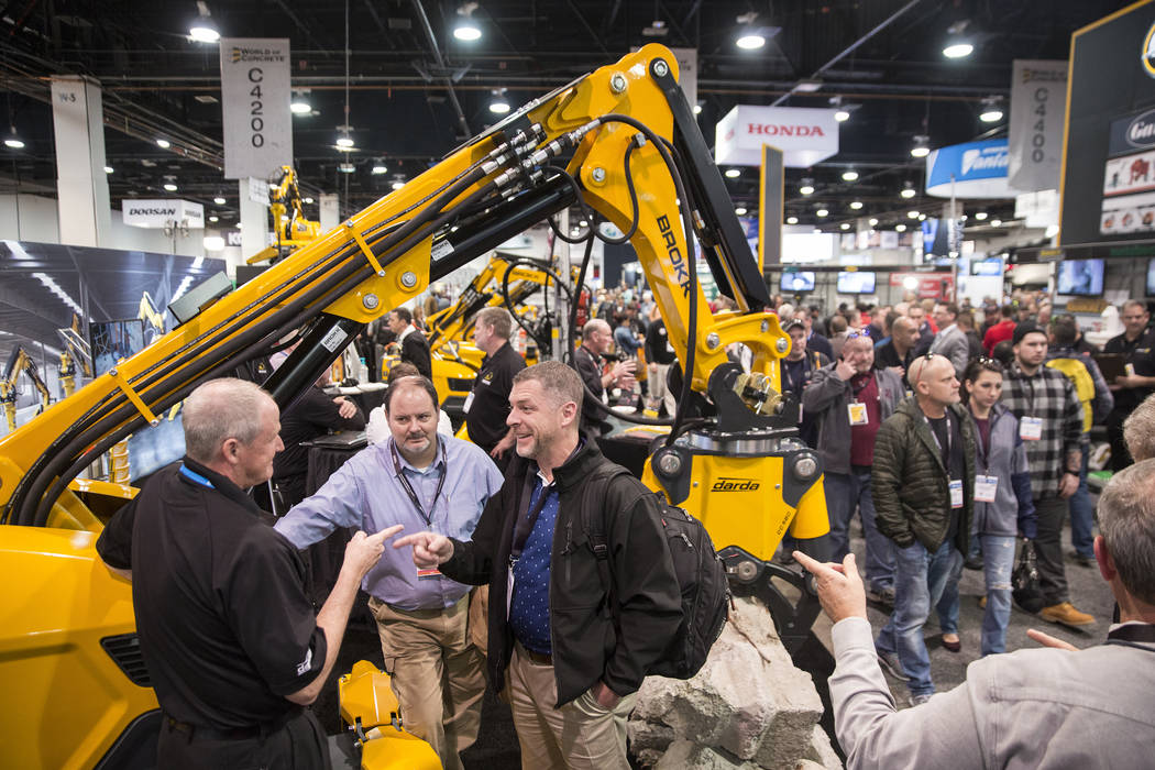 Clint Grimes, middle/right, and Jay Ambry, both with McClelland Marketing, speak with a sales representative with Brokk during the first day of the World of Concrete on Tuesday, Jan. 22, 2019, at ...