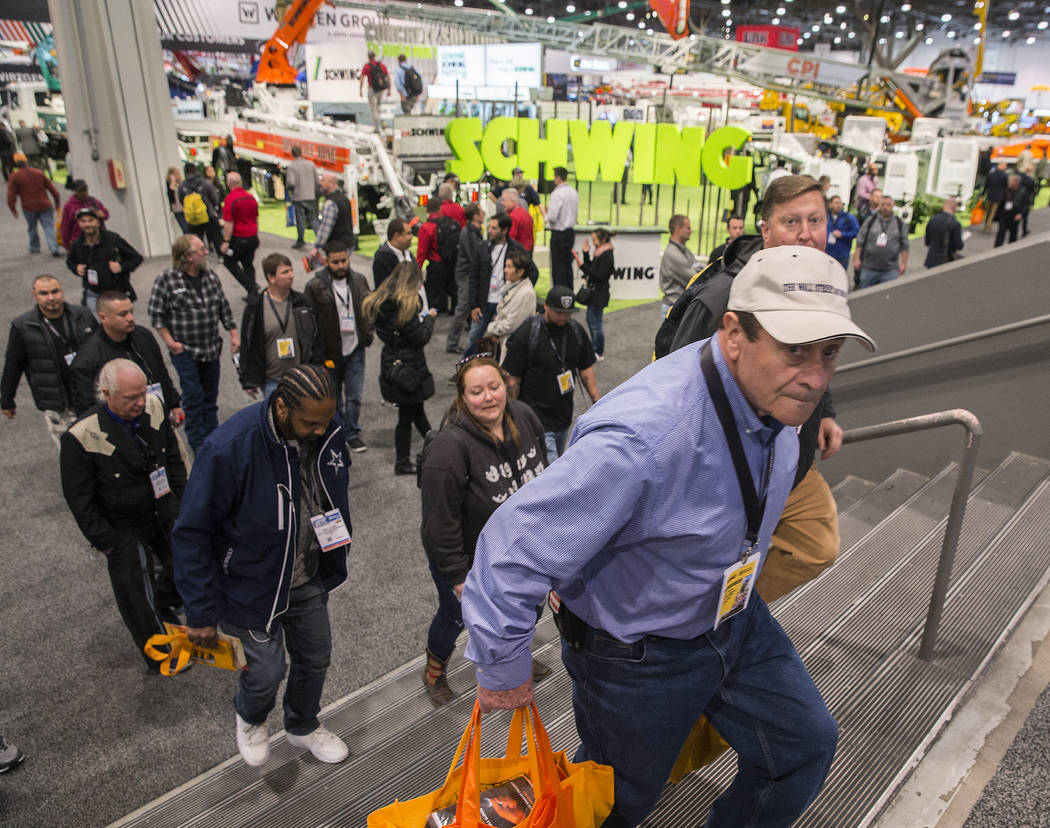 Antonio Castelluccio, right, with Castelluccio Construction, shops in the North Hall during the first day of the World of Concrete on Tuesday, Jan. 22, 2019, at the Las Vegas Convention Center, in ...