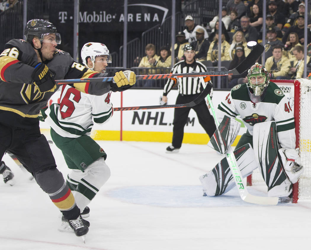 Golden Knights center Paul Stastny (26) fights for a loose puck with Minnesota Wild defenseman Jared Spurgeon (46) and goaltender Devan Dubnyk (40) in the first period on Monday, Jan. 21, 2019, at ...